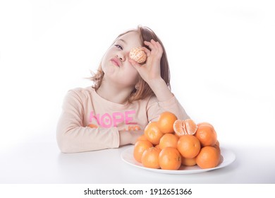 Young red haired child making a funny expression at the camera while holding a little orange mandarin. White background with healthy fruit and happy girl.