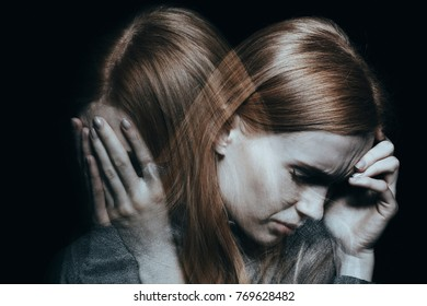 Young red haired female with mood disorder crying and having a headache