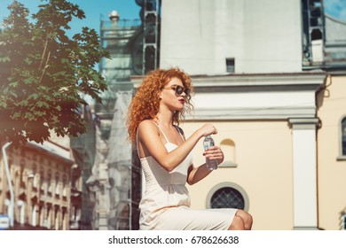 Young red haired girl drinking a bottle of water.