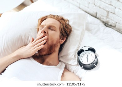 Young red haired man yawns lying in bed. Alarm clock rests pillow. Sweet dreams. Waking up. Napping.