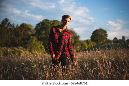 Young red haired woman posing in a cornfield while wearing flannel shirt