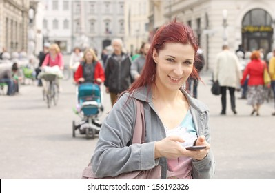 Young red haired woman using her mobile phone in a city centre, people walking in background