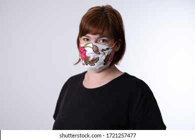Young red haired woman wearing self made face mask with rose pattern