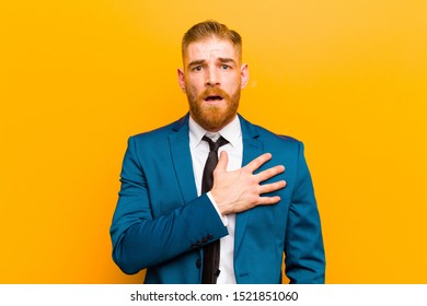 young red head businessman feeling shocked, astonished and surprised, with hand on chest and open mouth, saying who, me? against orange background