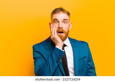 young red head businessman open-mouthed in shock and disbelief, with hand on cheek and arm crossed, feeling stupefied and amazed against orange background