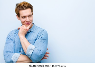 young red head man smiling with a happy, confident expression with hand on chin, wondering and looking to the side against blue wall