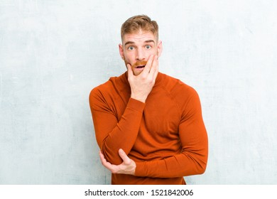 young red head man wearing turtle neck open-mouthed in shock and disbelief, with hand on cheek and arm crossed, feeling stupefied and amazed against concrete wall