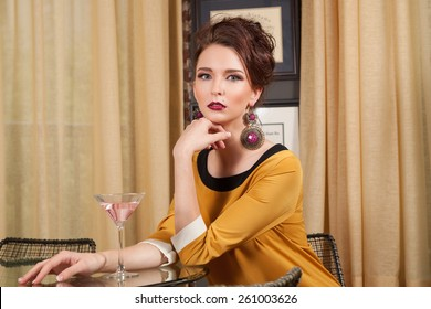 young red head in vintage 60's outfit sitting drinking