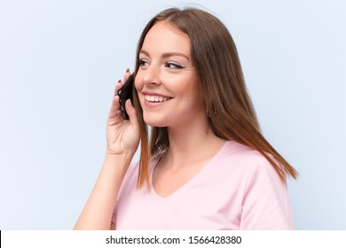 young red head woman  against flat wall with a smart phone