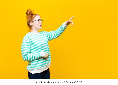young red head woman feeling shocked and surprised, pointing and looking upwards in awe with amazed, open-mouthed look against orange wall