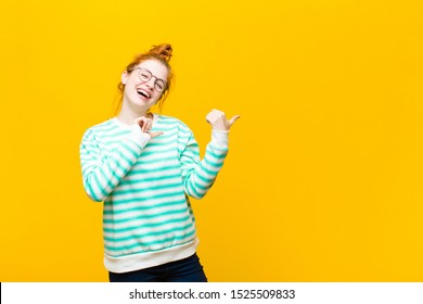 young red head woman smiling cheerfully and casually pointing to copy space on the side, feeling happy and satisfied against orange wall