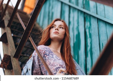 Young red headed gorgeous woman with photo camera sitting on a wooden stairs outdoors