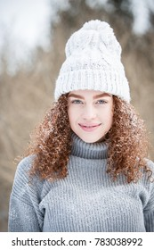 Young red headed woman in the snow wearing a hat.