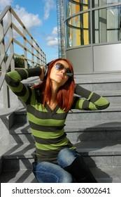 Young red woman enjoying music outdoors