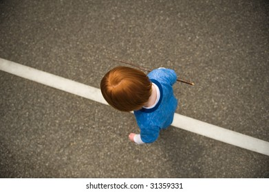 Young, red-haired boy walking along solid white road line.