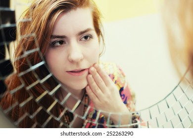Young red-haired girl doing morning makeup before the mirror