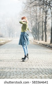 young red-haired girl rejoices and dances in the street, street dancer