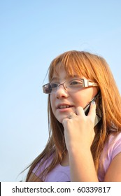 Young, red-haired girl talking on the phone