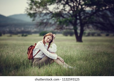 Young red-haired traveler in fairy-tale beautiful scenery. The idea and concept of rest, relaxation, freedom