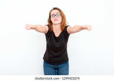 Young red-haired woman with glasses in doubt on a light background. Confusion, insecurity, thinks.