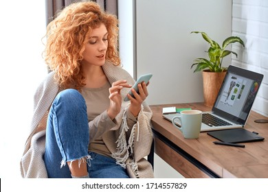 Young red-haired woman graphic designer working from home side hustle drinking hot coffee browsing internet on smartphone smiling curious