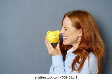 Young red-haired woman kissing yellow piggy bank against blue background