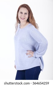 Young red-haired woman with long hair posing on a white background with smiling and happy attitude