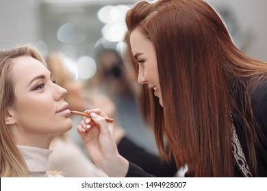Young red-haired woman make-up artist puts make-up on the face of a beautiful blonde girl in a beauty salon. Concept of personal care and celebration preparation