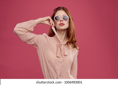 young red-haired woman on a pink background