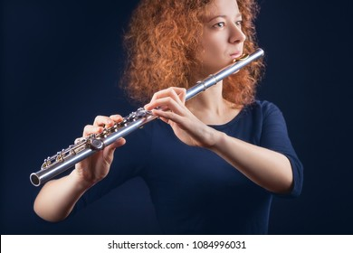Young red-haired woman woman playing the flute on black background