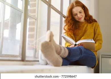 Young red-haired woman reading book while sitting on windowsill