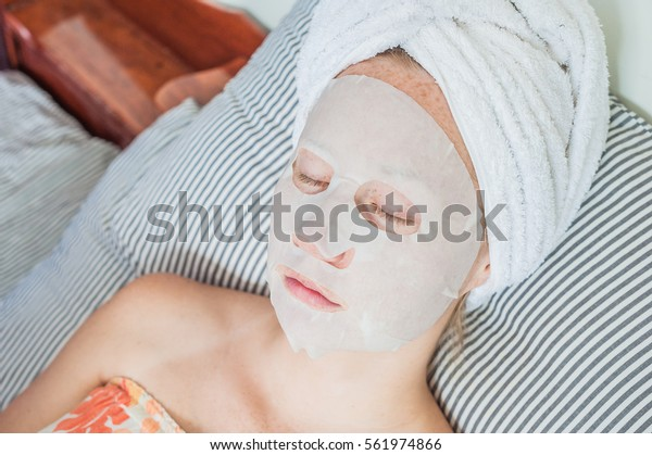Young red-haired woman relaxing on a bed. Sheet mask on her face. Beauty and Skin Care Concept