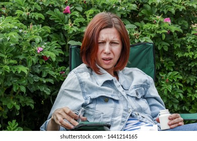 Young red-haired woman sits in a chair and takes pills. Summer exacerbation of the disease. Drug treatment. Pain and suffering. Painful appearance. Taking medicine with disgust. Unpleasant taste pills