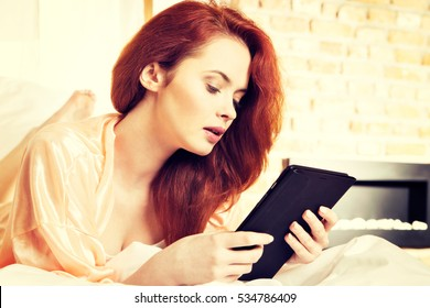 Young red-haired woman using computer tablet browsing internet. Girl laying in bed holding ebook. Relaxing concept. Toned image