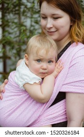 Young redhead babywearing mother carry her sleepy one year old baby girl in a pink wrap sling