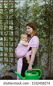 Young redhead babywearing mother carry her sleepy one year old baby girl in a pink wrap sling while gardening