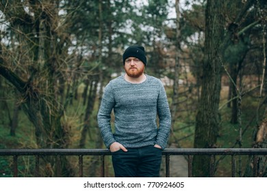 young Redhead  bearded in a sweater  and cap, outside