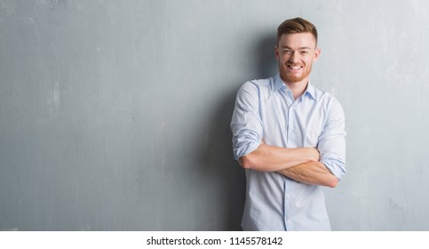 Young redhead business man over grey grunge wall happy face smiling with crossed arms looking at the camera. Positive person.