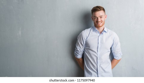 Young redhead business man over grey grunge wall with a happy and cool smile on face. Lucky person.