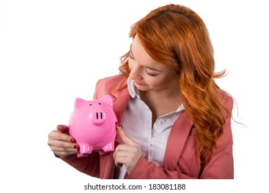 Young redhead business woman holding and showing pink piggy bank, isolated on white background.