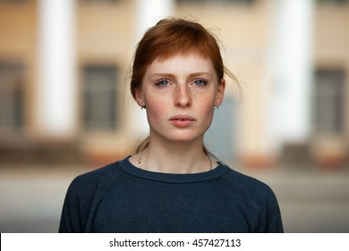 Young redhead caucasian woman serious face outdoor portrait