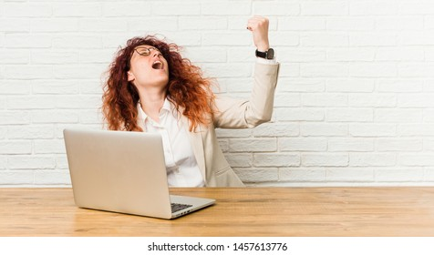 Young redhead curly woman working with her laptop raising fist after a victory, winner concept.