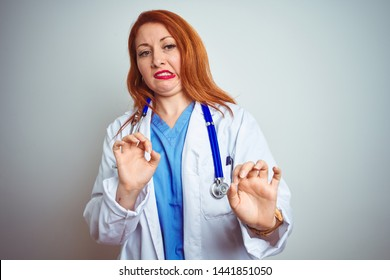 Young redhead doctor woman using stethoscope over white isolated background disgusted expression, displeased and fearful doing disgust face because aversion reaction. With hands raised. Annoying