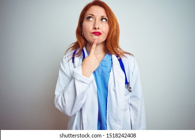 Young redhead doctor woman using stethoscope over white isolated background Thinking concentrated about doubt with finger on chin and looking up wondering
