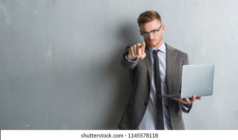 Young redhead elegant business man over grey grunge wall using laptop pointing with finger to the camera and to you, hand sign, positive and confident gesture from the front