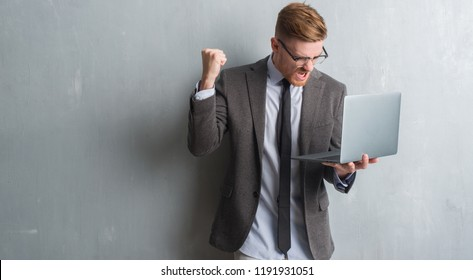 Young redhead elegant business man over grey grunge wall using laptop annoyed and frustrated shouting with anger, crazy and yelling with raised hand, anger concept