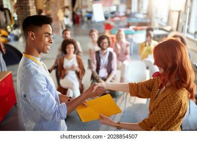 una joven pelirroja felicita a un estudiante por asistir exitosamente a un seminario de negocios, dándole un certificado en carpeta. imagen de enfoque selectivo.