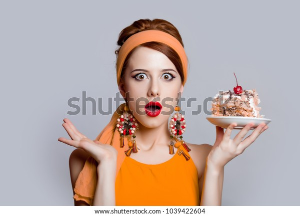 Young redhead girl in 70s clothes style with cake on grey background