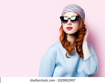 Young redhead girl in beautiful blue clothes in sunglasses on pink background