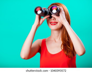Young redhead girl with binoculars on mint background